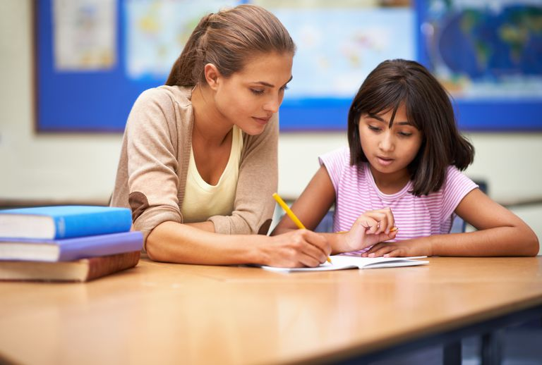 Teacher with student writing in notebook