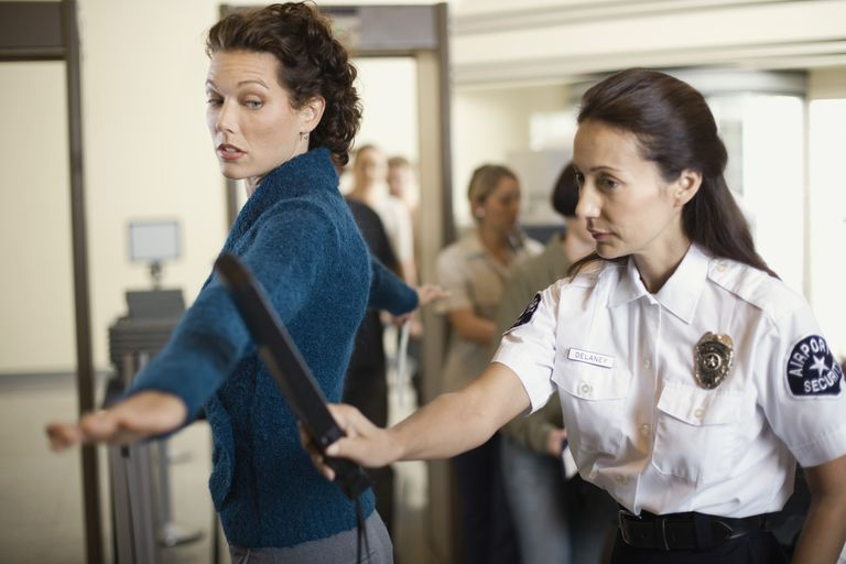 Security officer searching businesswoman at airport