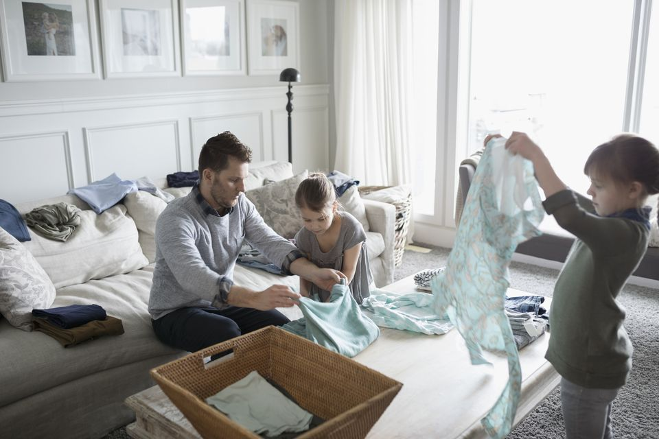 Father and daughters folding laundry in living room