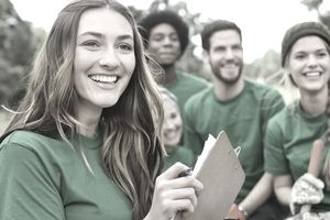 Woman holding clipboard leading volunteers outside