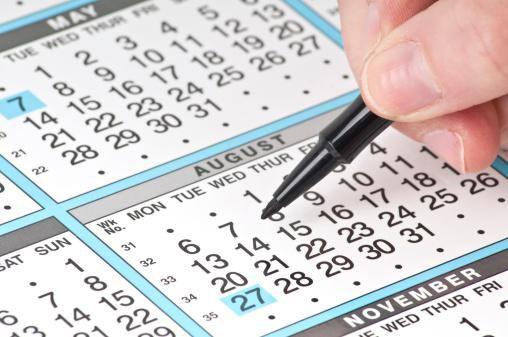 Person holding felt-tip pen over calendar
