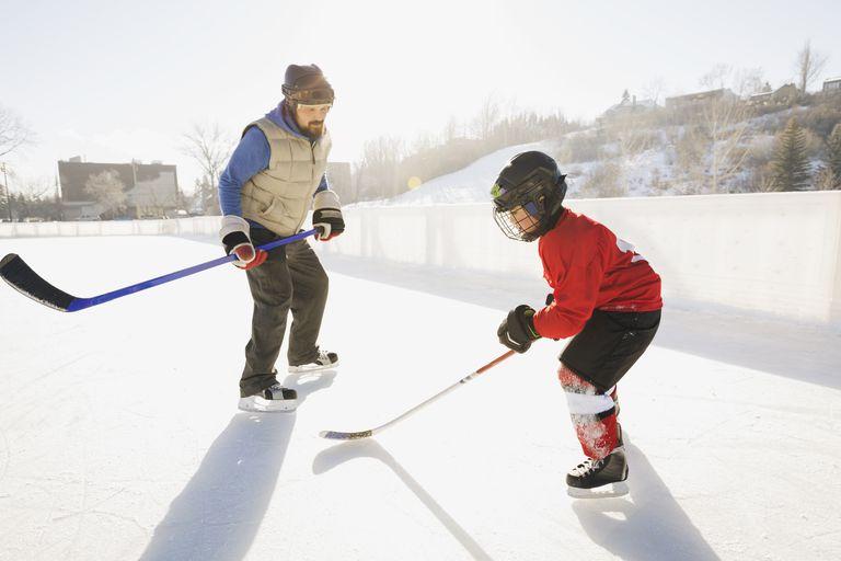 Coach training ice hockey player on rink