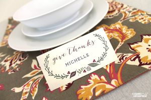 "A ""Give Thanks"" place card by a table setting."