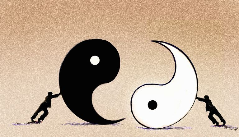 Businessmen pushing yin and yang symbols together.