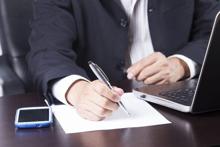 man signing letter
