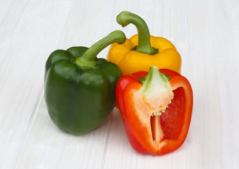 Three colourful, organic bell peppers on white