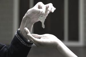 Detail of realtor handing keys to new home owner