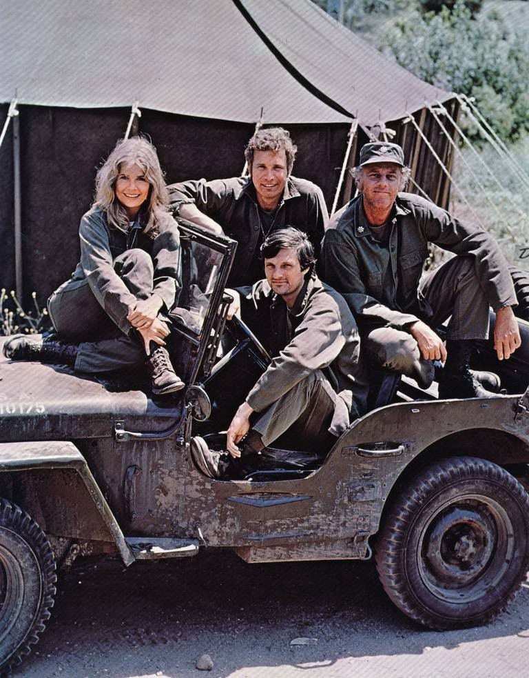 A picture of the actors of MASH sitting in a jeep.