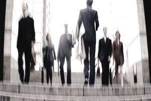 Businesspeople walking through square (defocussed)