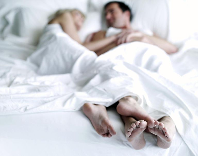 Man and woman lying in bed, focus on feet