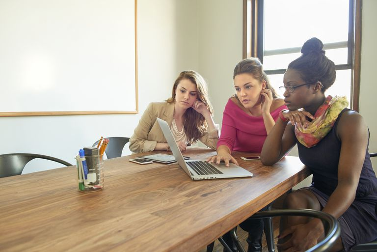 3 young female entrepreneurs discuss plans to launch startup company.