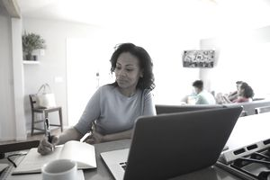 a woman working from home on a laptop with children in the background