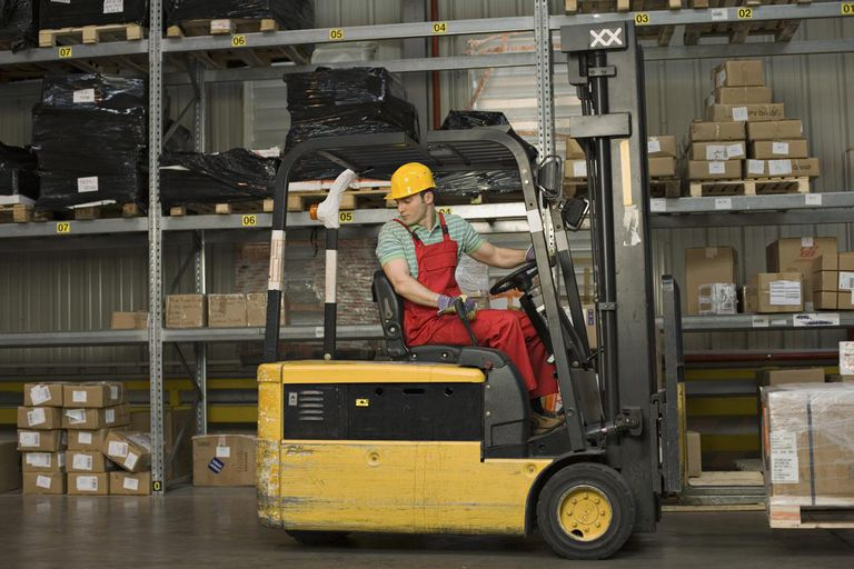 Worker with forklift moving boxes