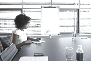 Black Business Woman writing in paper at desk with pen