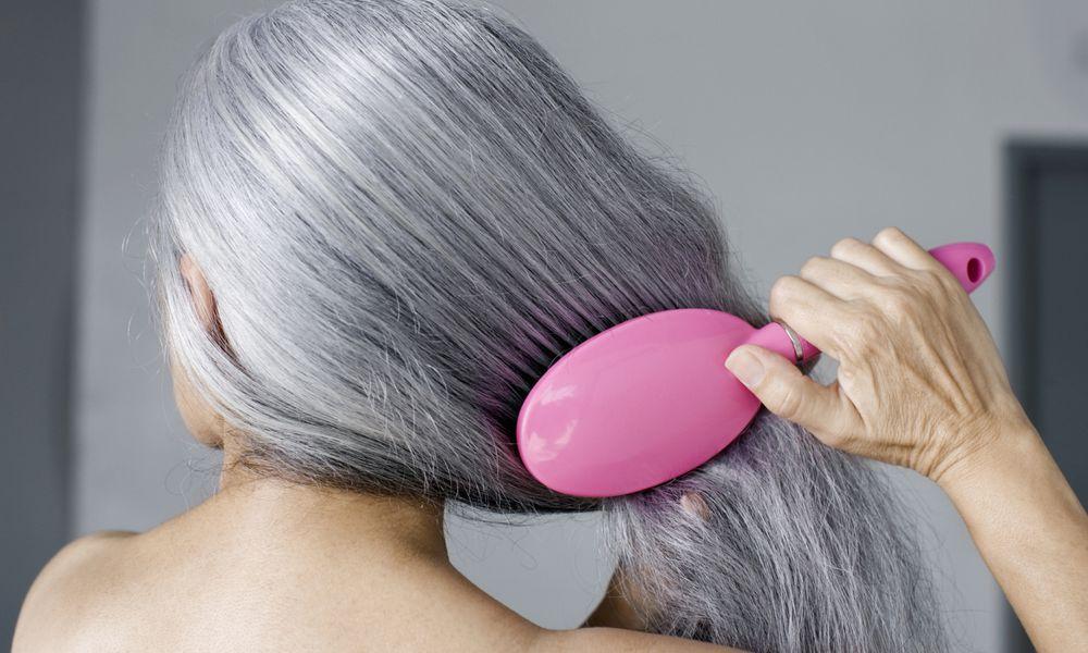mature woman brushing hair