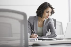 Woman reviewing resumes and taking notes