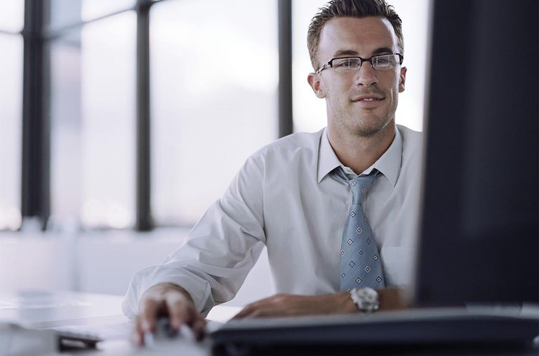 Picture of a male office worker at workstation, hand on computer mouse