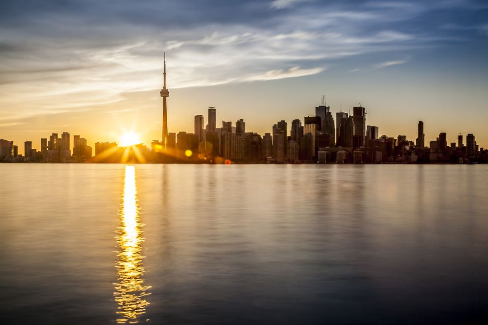 The sun setting behind the City of Toronto, Ontario as seen from Algonquin Island - one of the Toronto Islands