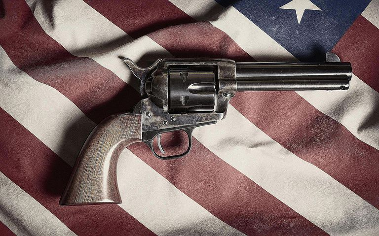 A Colt Peacemaker set atop the American flag symbolizes the association of gun ownership with being American and having pride in the country. Learn the demographics behind gun ownership here.