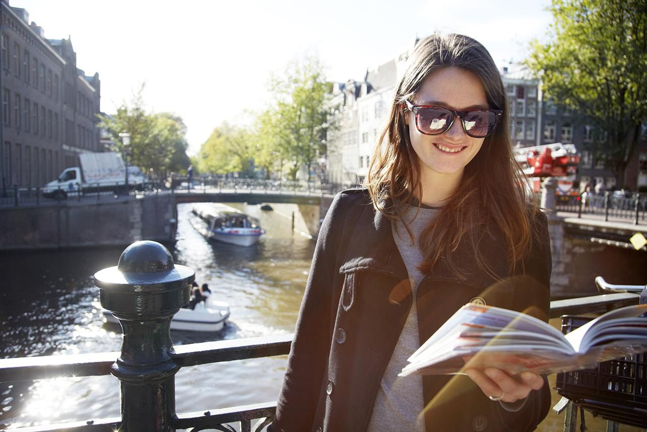 European clothing sizes and size conversions young woman on bridge with guidebook geenschuldenfo Images