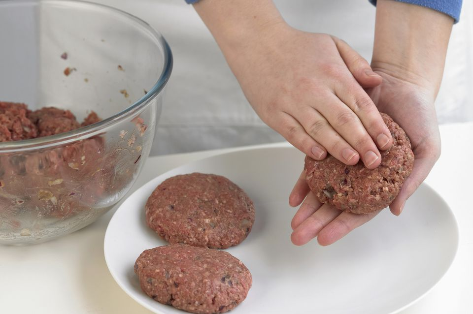 Woman making beef burger