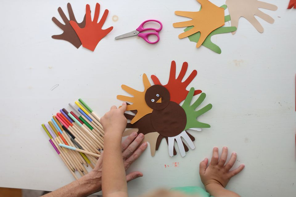 Students and teacher making Thanksgiving turkey crafts in classroom