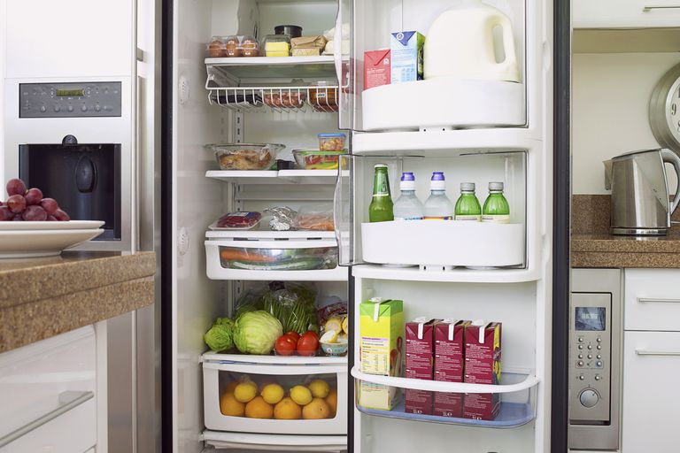 Food and drink in full domestic refrigerator with open door