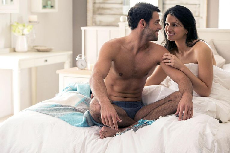 Happy young couple cuddling in bed together.
