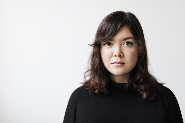 Portrait of serious young woman against white background