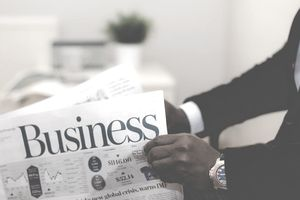 business man holding business section of newspaper