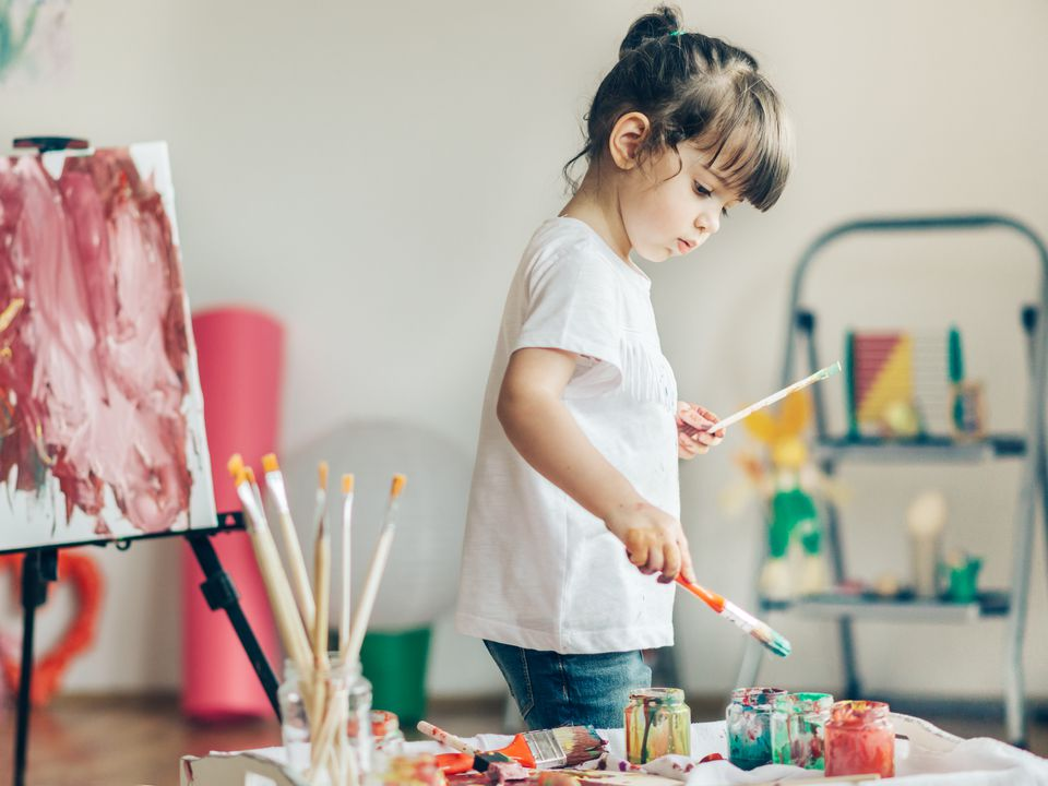 Cut girl painting in at her home.