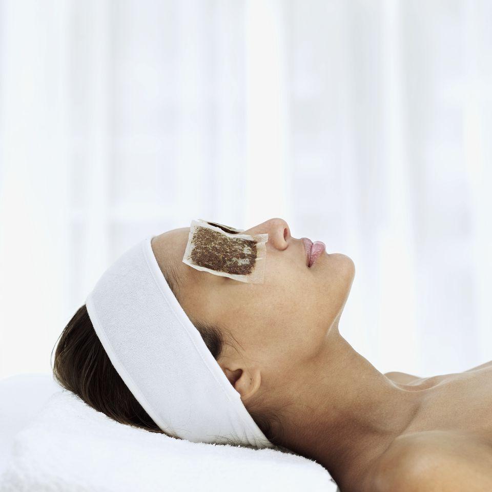 Woman lying with tea bags on eyes