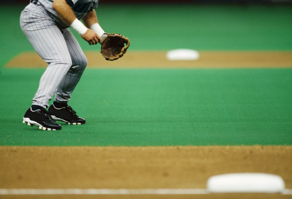 Baseball player standing in infield, low section, side view