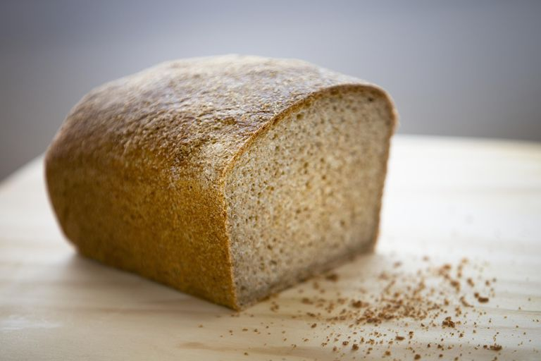 Whole wheat bread on chopping board, close-up
