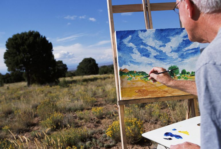Mature man painting picture in field