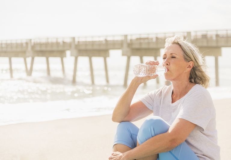 USA, Florida, Jupiter, Senior woman drinking water on beach
