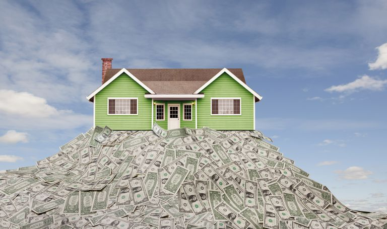 House sitting on pile of dollar bills