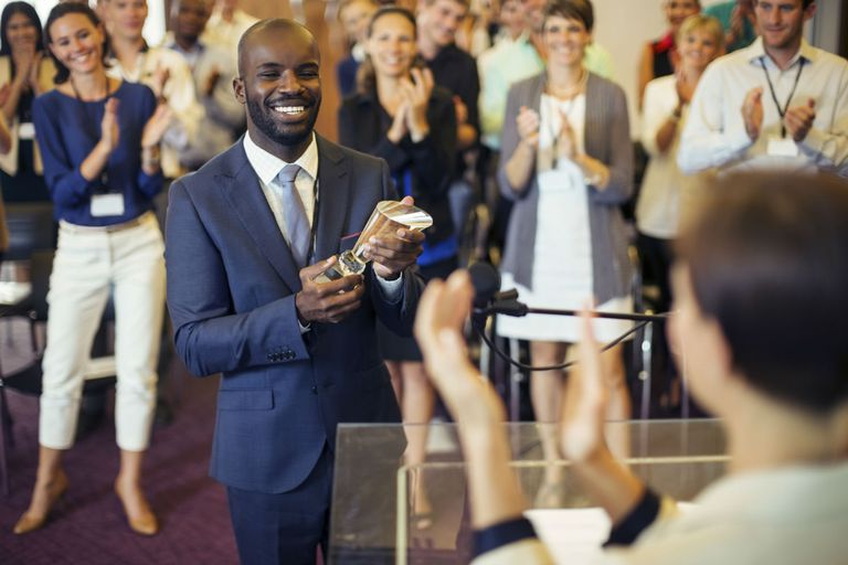 Business professional accepting award from boss with clapping co-workers in the background