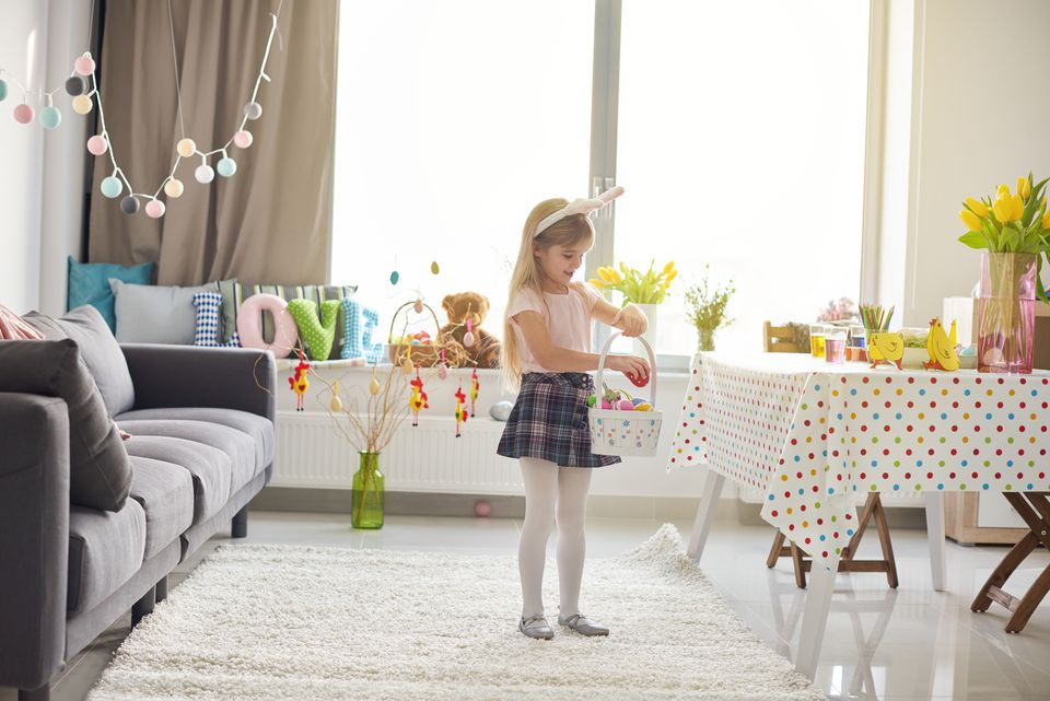 Girl placing easter eggs into basket in living room