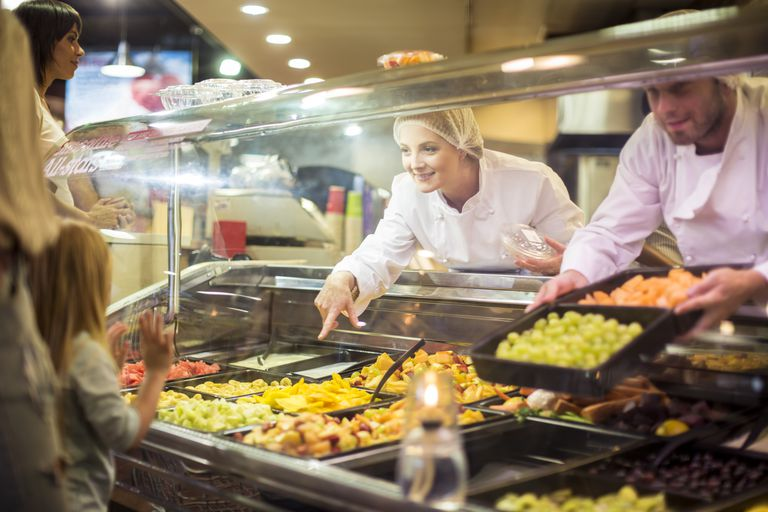 Customers choosing food from display at supermarket