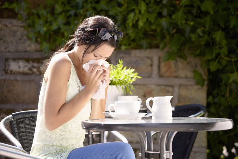 Woman sitting at table with allergies