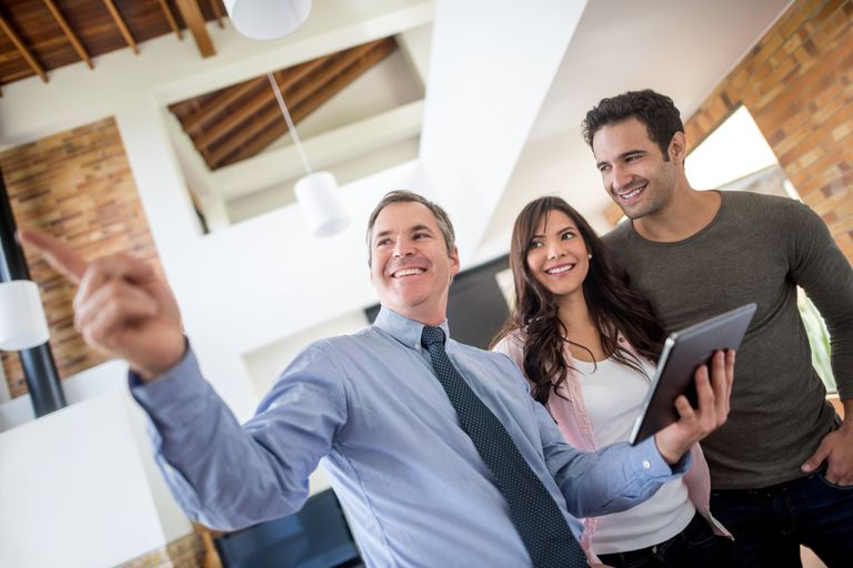 real estate agent showing building to couple
