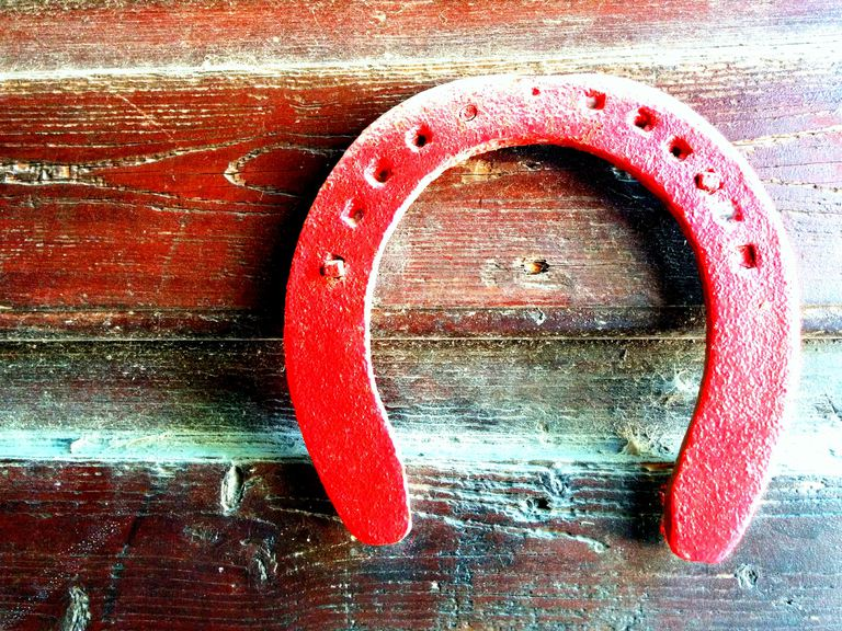 Close Up Of Red Horseshoe On Wooden Wall