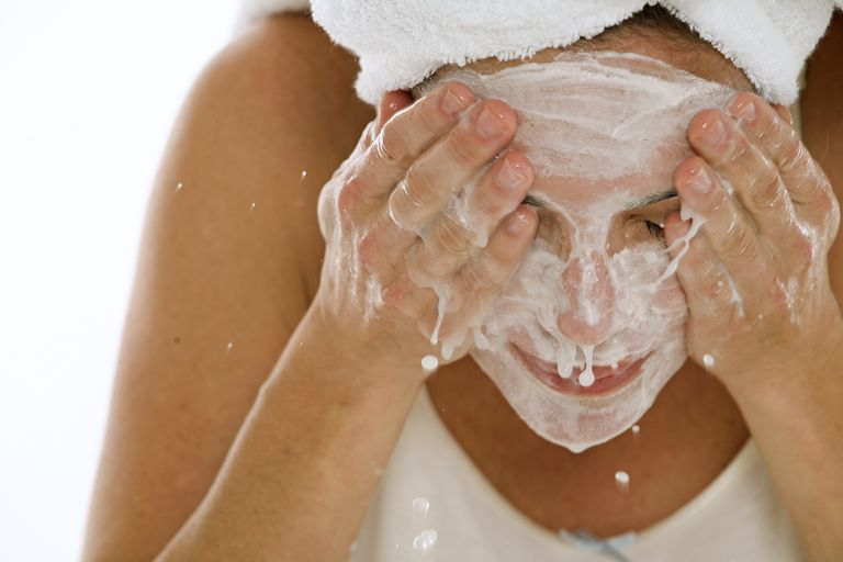 Close-up of a young woman splashing water on her face