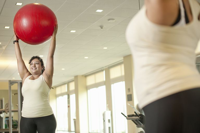 Woman in gym holding exercise ball over her head