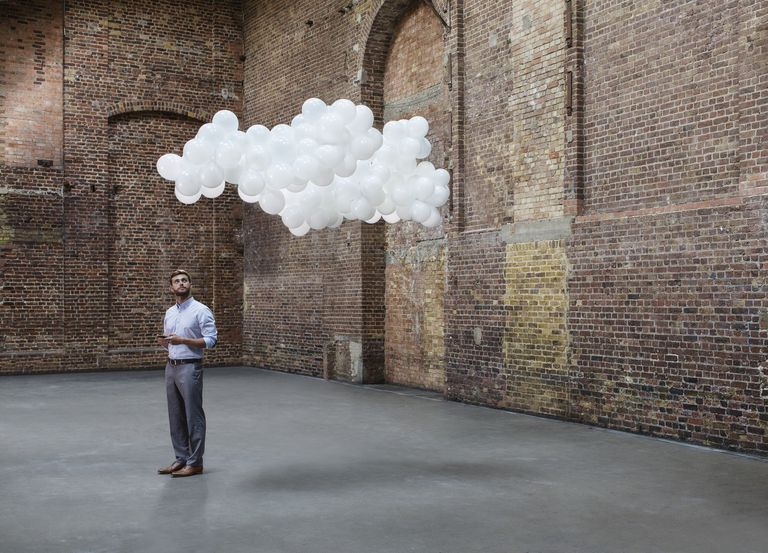 man looking up at cloud overhead
