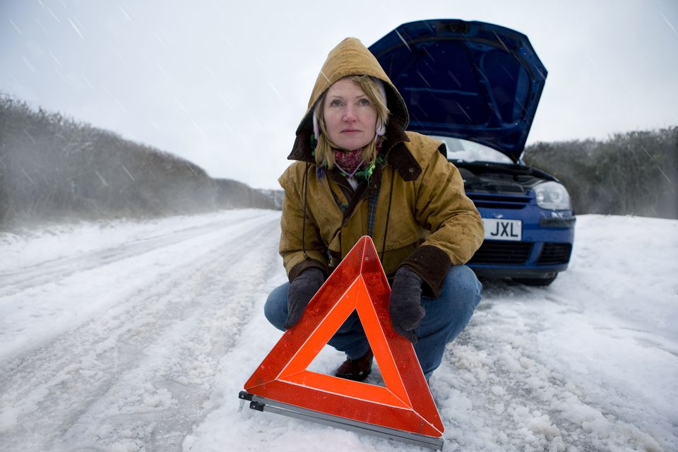 Woman with broken-down car placing emergency reflective triangle on snowy road