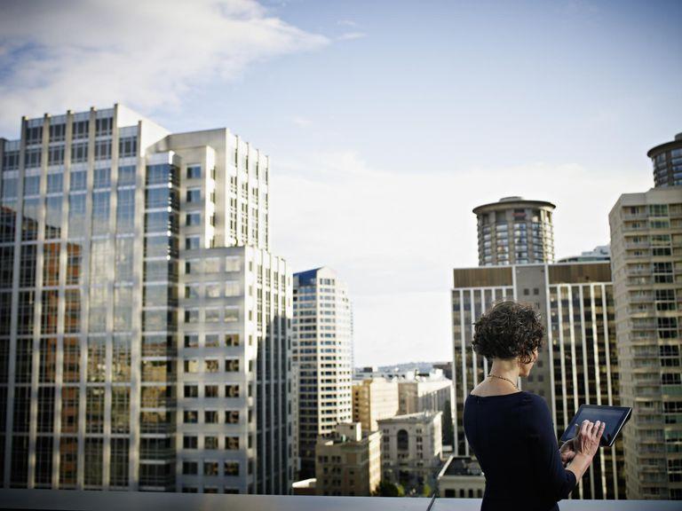 Mulher de negócios trabalhando em tablet digital no convés de escritório com vista para a cidade