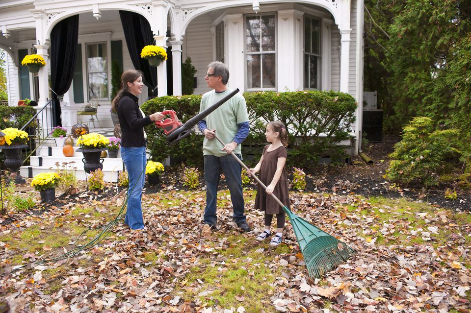 family blowing and raking leaves