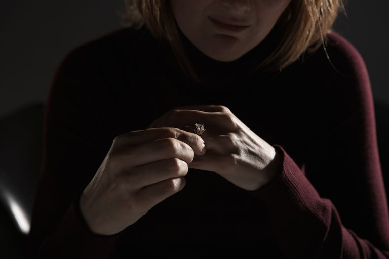 Woman adjusting wedding ring, mid section (focus on hands)